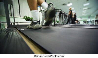 feet of man go on treadmill in large gym
