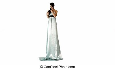 Unusually tall brunette model in long dress stands isolated