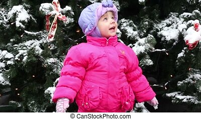 Little girl stands and look toward in front of Christmas tree covered with snow