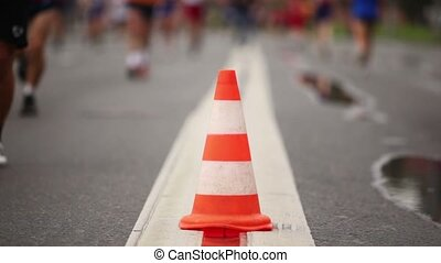 Big orange cone on road between running people