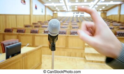 Microphone in hall and a hand which taps on it close up -...