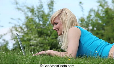 Woman lying in the grass with a lap