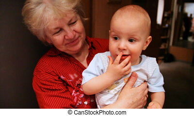grandmother hold baby in hands and smiling at home