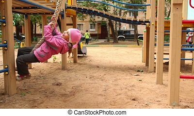 Little girl sway on rope at playground at sunny autumn day