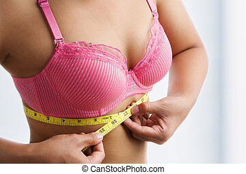 Woman measuring breast band size