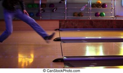 Two men throw bowling ball on parallel lanes in club