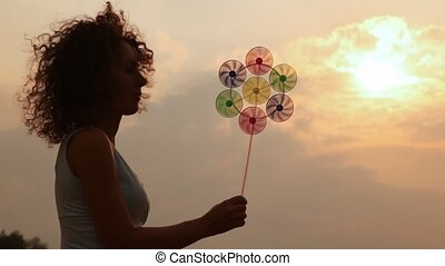 woman holds childrens windmill and smiles - woman against...