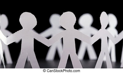 many paper people stand in circle and hold hands, rotates on...