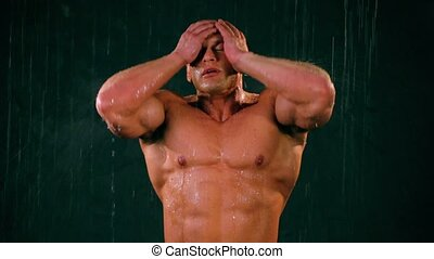 Bodybuilder stands under water jets, wash his body and turn...