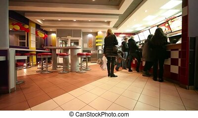Several people stand in front of counter in cafe - Several...