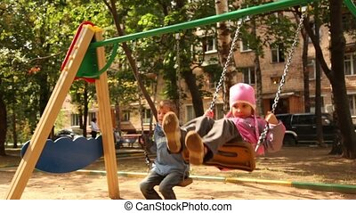 Boy and little girl sway on swing at playground, then boy...
