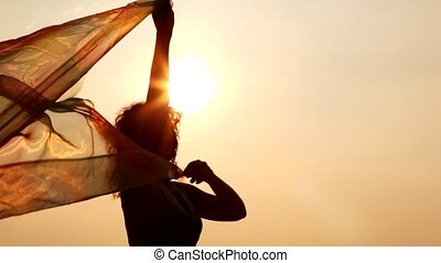woman against sky and sun has hold thin shawl which waves on...