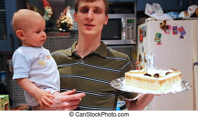 little baby in fathers hands try catch birthday cake on one...