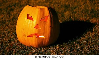 Scary Jack O-Lantern halloween pumpkin with flame inside, on...