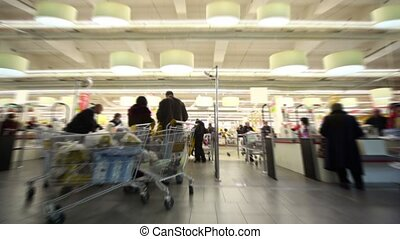 People with baskets on supermarket cash-desk