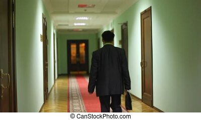 behind deputy assistant walking away along corridor and...