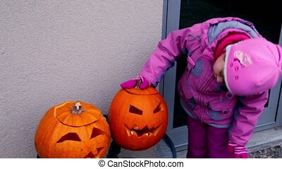 Little girl watch on two halloween pumpkin heads - Little...