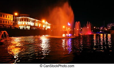 boat quickly moves along Moscow River near beautiful lighted...