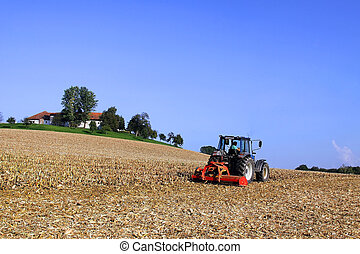 farmer with tractor on field - a farmer with his tractor at...