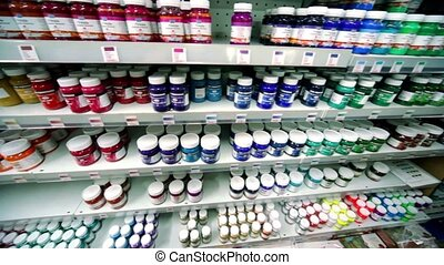 Many cans of paint are on shelves in store, shown in motion