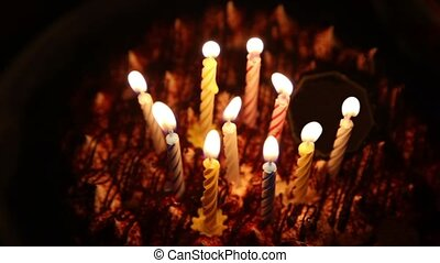 Happy Birthday cake with burning spiral candles which are...
