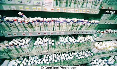 Many tubes of paint are on shelves in store, shown in motion