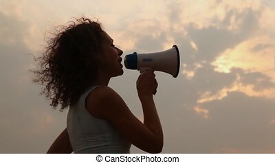 woman stands and tells something in megaphone lifts it...