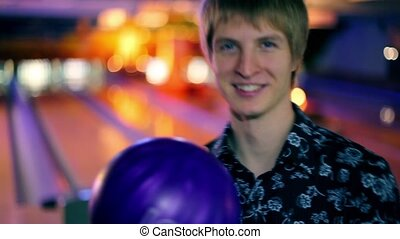 boy hold bowling ball, and then throws it to beat skittles -...