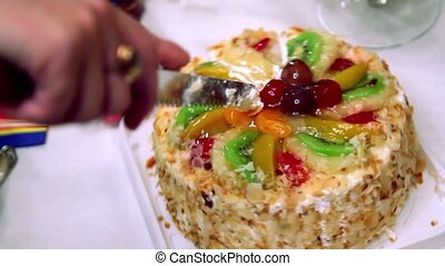 Hands severs sweet fruit cake by knife, close-up view