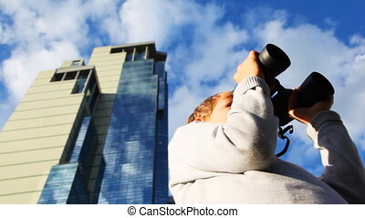 inquisitive boy looks through binoculars and turns on background of skyscrapers