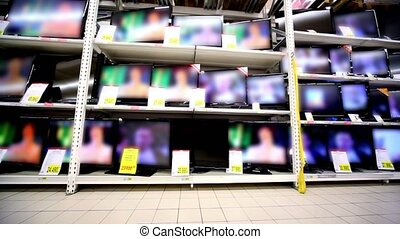 Many tv sets stay working on showcase in hypermarket