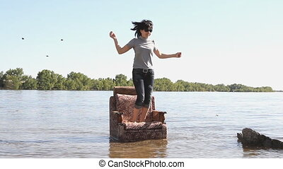 Girl jumping on a chair standing in the river