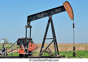 Old Pump Jack - Old rusty oil pump jack against a blue sky...