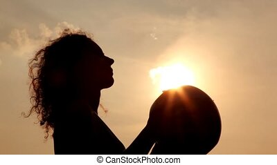 woman throws ball against sky and sun so their silhouette is...
