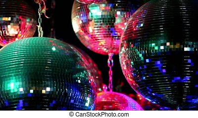 Several discoballs hang on chain and rotate, light is...