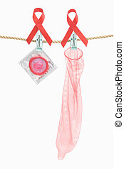 Condom hanging with red ribbon over white background, a...