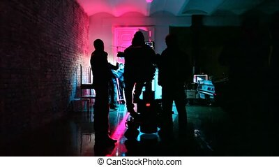 operator with videocamera and film crew in almost dark room prepare scenery