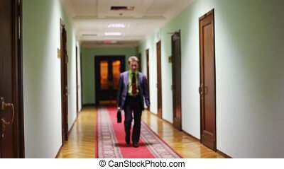 deputy smiling assistant approaching along corridor - Young...