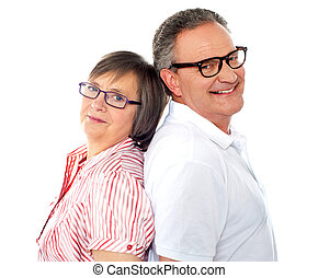 Portrait of smiling aged couple posing back to back against...
