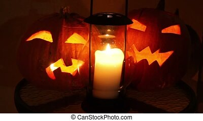Two pumpkins of halloween with flame inside and old candle lamp