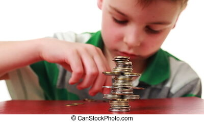 boy makes highly complicated figure with coins on red base,...