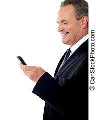 Business executive reading text sms on his cellphone, studio...