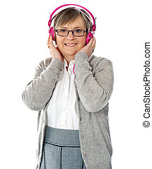 Attractive old lady wearing headphones listening music