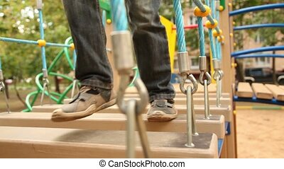 Little girl and boy walk on hang down steps at playground,...