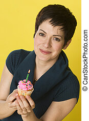 Her Cupcake - A woman smiles before blowing out her candle...