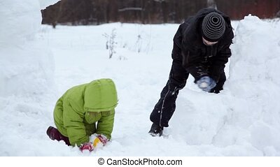 Brother and sister play with snow in park at winter