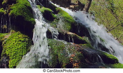 Waterfall in spring forest. Shot with slider. Slow-motion.