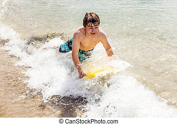 happy boy enjoys surfing in the waves at the beach