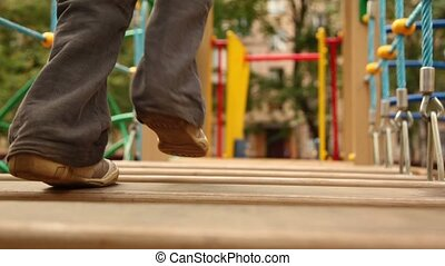 Little girl run on hang down wooden steps few times at playground