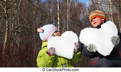 little boy and girl hold heart made of snow in winter